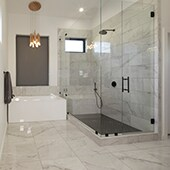 Bathroom with large format marble look porcelain tile flooring and shower walls
