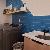 Laundry room with blue and white rectangular tile on the wall
