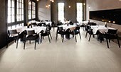 Restaurant dining area with smooth, beige stone look tiles on the floor and walls